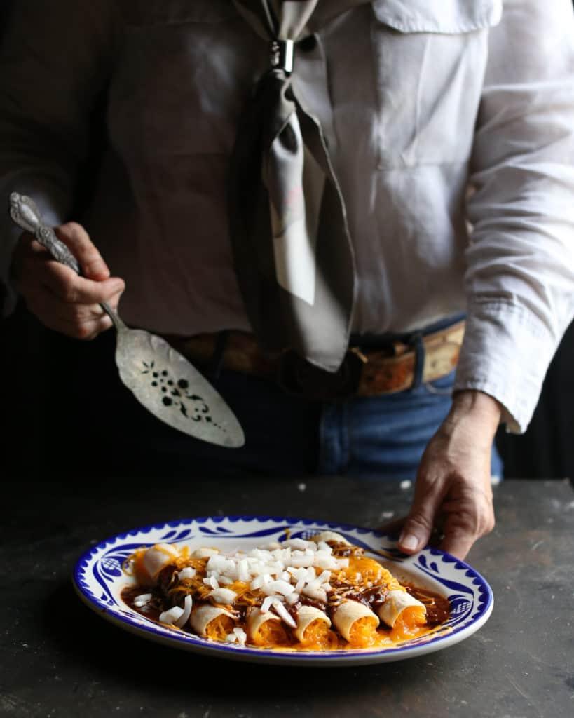 hands serving enchiladas